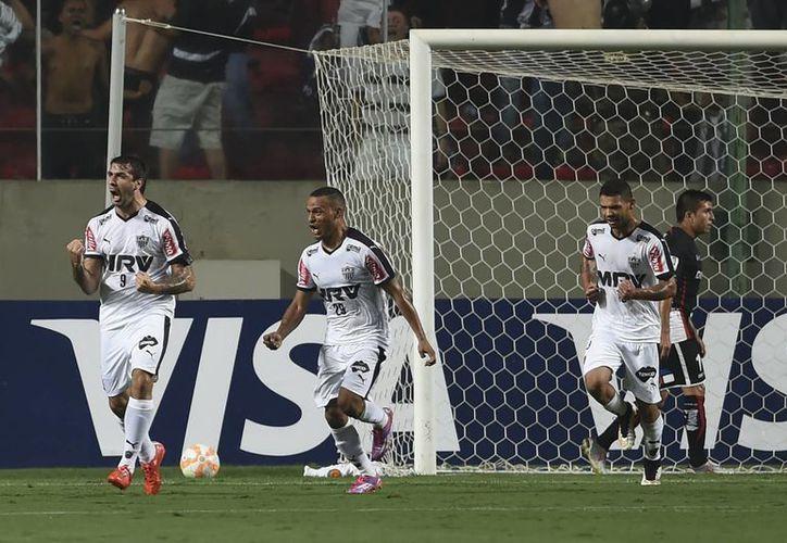 Lucas Pratto (i) se dispone a celebrar su gol con sus compañeros de Santa Fe, club colombiano que ganó 3-1 y eliminó al Atlas mexicano de Copa Libertadores. (Foto: AP)