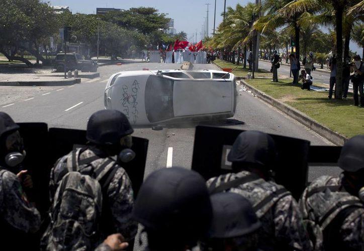 Los manifestantes volcaron un automóvil de un canal de televisión local al que luego incendiaron. (Agencias)