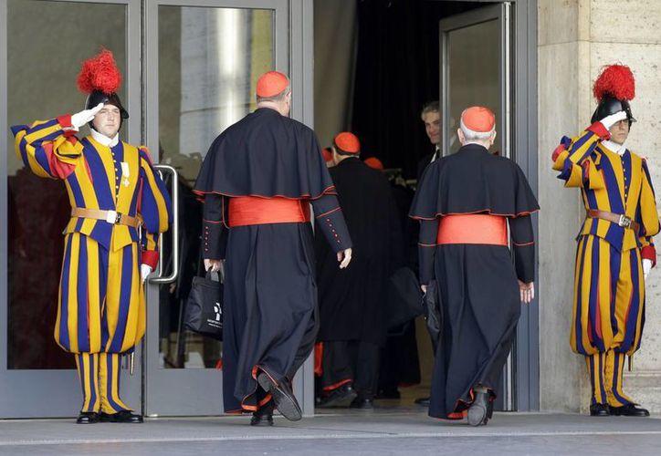 Guardias suizos saludan a varios cardenales que llegan a una reunión en el Vaticano. (AP)