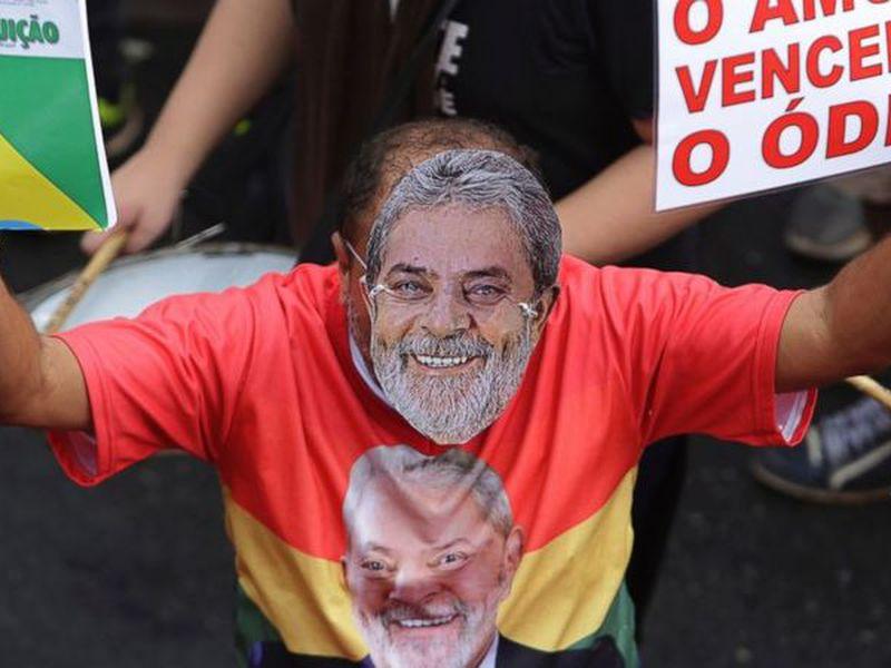 A demonstrator wearing a mask depicting former Brazilian President Luiz Inacio Lula da Silva.