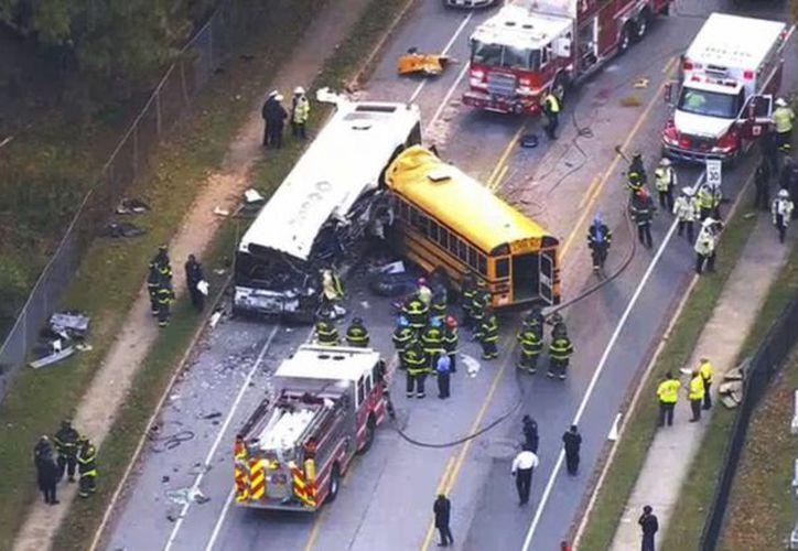 En esta imagen tomada de un video, personal de emergencia trabaja en la escena de un choque fatal de un autobús escolar y uno de pasajeros en Baltimore. (WBAL-TV via AP)