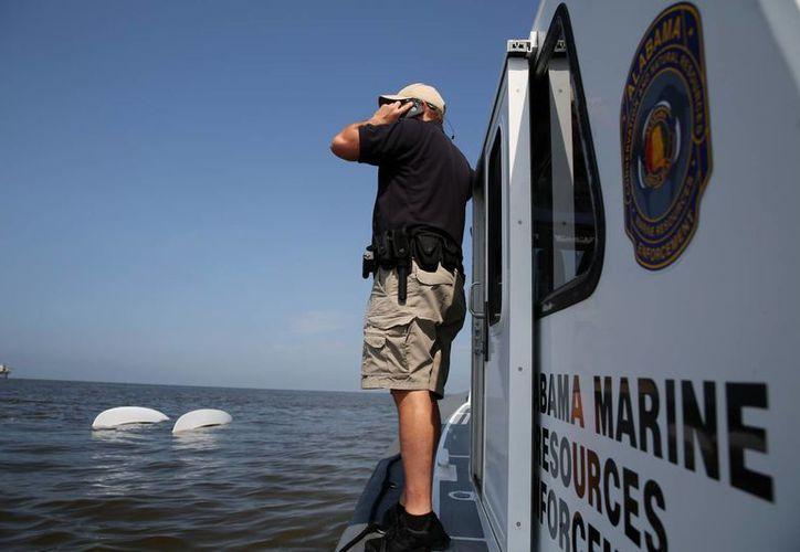 El teniente Jason Downey, del Departamento de Conservación de Recursos Naturales en Alabama, participa en labores de búsqueda y rescate de veleristas sobrevivientes de un naufragio. Al fondo se ve un catamarán volcado. (Foto: AP)