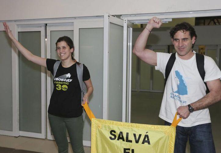 """Los dos tripulantes argentinos del rompehielos """"Arctic Sunrise"""" de Greenpeace, Camila Speziale y Hernán Pérez Orsi, fueron recibidos por familiares y activistas de Greenpeace, a su llegada a Buenos Aires. (EFE)"""