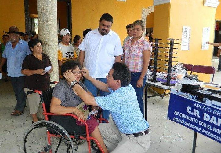 El senador Daniel Ávila entrega lentes graduados a Rosa Basilia Poot Chan, vecina de Tixkokob. (SIPSE)