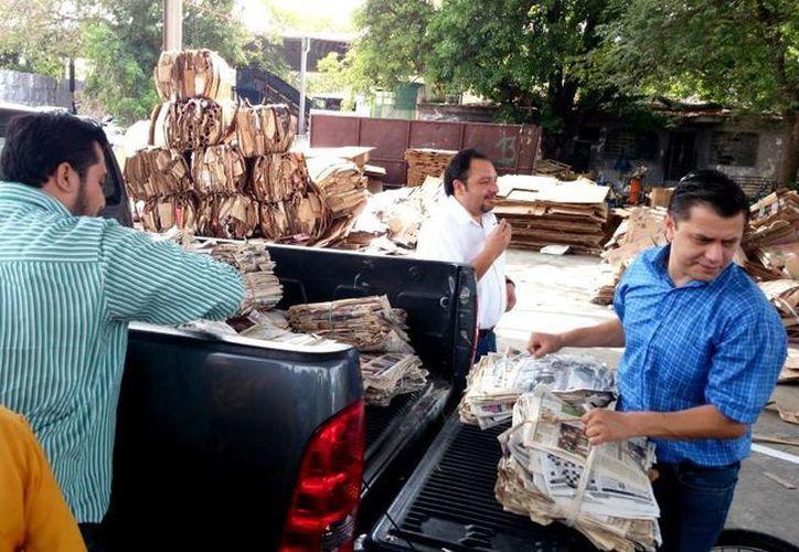 Colaboradores del diputado Francisco Torres ayudan a descargar el periódico de reciclaje de don Luis Ojeda Cortés. (SIPSE)