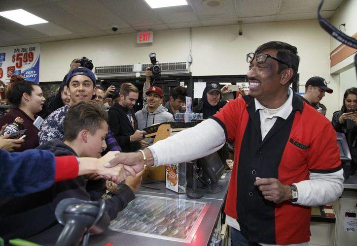 Una multitud felicita a M. Faroqui, empleado del establecimiento donde se vendió una de los tres boletos ganadores de lotería con el mayor premio de la historia de Estados Unidos; 1.500 millónes de dólares, en Chino Hills, California, el 13 de enero de 2016. (EFE)