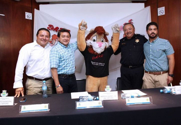 Darío, mascota del Programa D.A.R.E., y funcionarios del ayuntamiento de Mérida informaron los detalles de la segunda jornada deportiva de este año. (SIPSE)