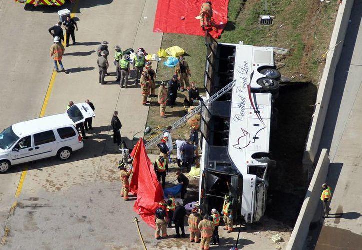 Equipos de emergencia rescataron a los viajeros a través de las ventanas del autobús. (Agencias)