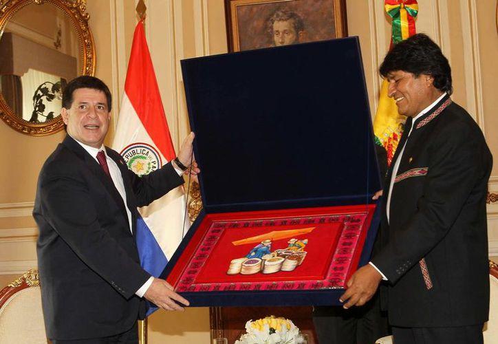 El presidente de Paraguay, Horacio Cartes (izq), recibe un regalo de su homólogo boliviano, Evo Morales, en el Palacio de Gobierno en La Paz, Bolivia. (EFE)