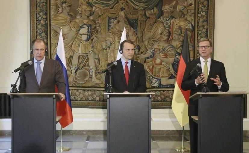 Los ministros de Exteriores alemán, Guido Westerwelle (d), ruso, Serguéi Lavrov (i), y polaco, Radoslaw Sikorski (c), dan una rueda de prensa conjunta tras su encuentro en Varsovia. (EFE)