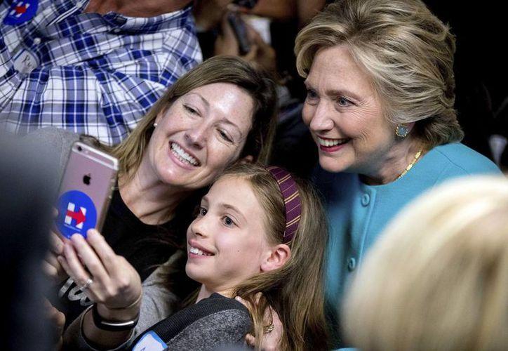Hillary Clinton se toma una selfie con una mujer y su hija durante un acto de campaña en Seattle, el pasado viernes. Una nueva encuentsa publica el 17 de octubre de 2016, da amplia ventaja a la candidata demócrata sobre Donald Trump, entre votantes hispanos. (Foto: AP/Andrew Harnik)
