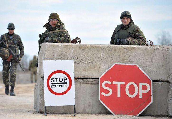 Soldados ucranianos vigilan en un retén, cerca de la frontera con Crimea, en el área de Kherson. (EFE)