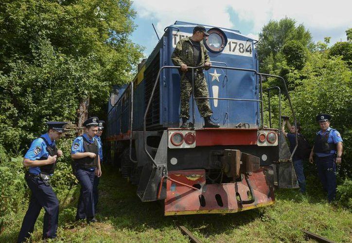 Tras el derribo del avión comercial con 298 pasajeros, autoridades comenzaron el traslado de los restos en un tren refrigerado. En la foto, en Jarkiv, Ucrania. (Foto: AP)