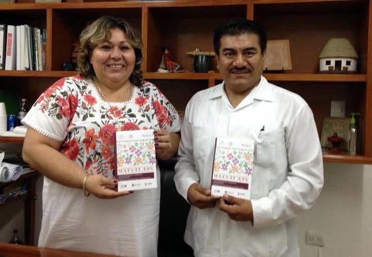La titular del Indemaya, Elizabeth Gamboa Solís, y el coordinador de Lingüística del INAH, con el libro 'Normas de escritura para la lengua maya'. (Milenio Novedades)
