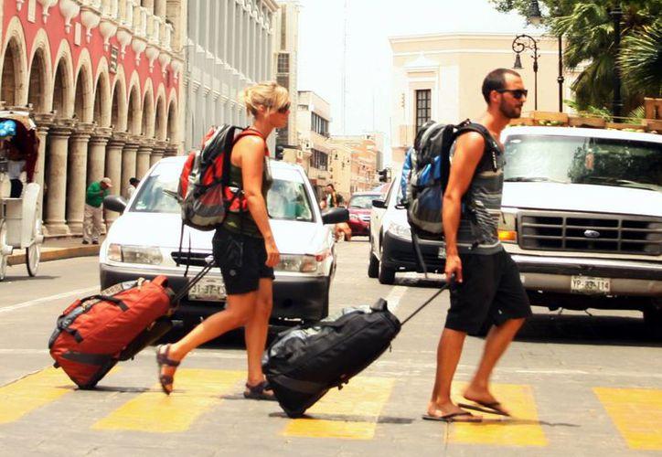 El turismo extranjero, con gran presencia en Yucatán para el fin de año. Imagen de dos turistas con maletas cruzando una calle, en el primer cuadro de la ciudad. (Milenio Novedades)