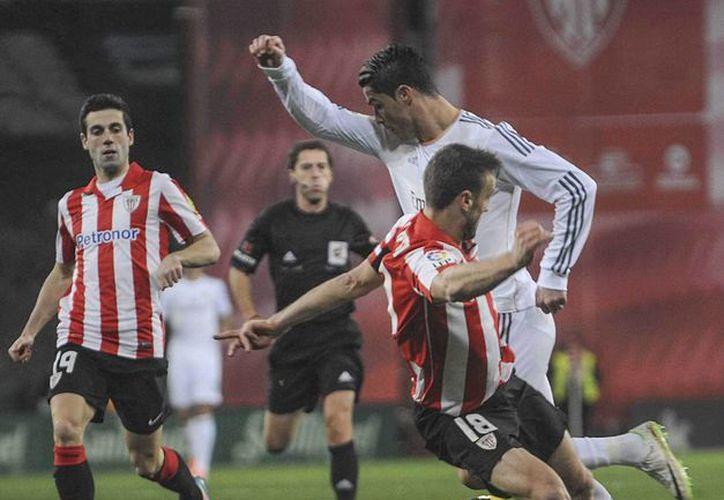 El delantero portugués del Real Madrid Cristiano Ronaldo (d) supera la entrada de Carlos Gurpegi (c), del Athletic de Bilbao, durante el partido del domingo de la Liga en Primera División. (EFE)