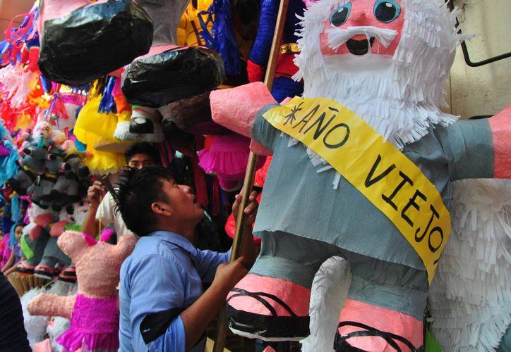 Para este Fin de año se esperan un gran número de celebraciones familiares en la calle junto con los vecinos, donde se acostumbra a quemar un 'viejo'. Imagen de una piñata acorde a la fecha en la calle Ancha del Bazar de Mérida. (Notimex/Archivo)