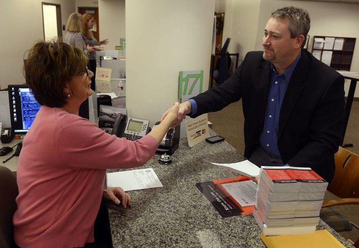 Shawn Phillips (der) propietario de Strainwise tiendas de marihuana, tras recibir su permiso para vender marihuana. (Agencias)