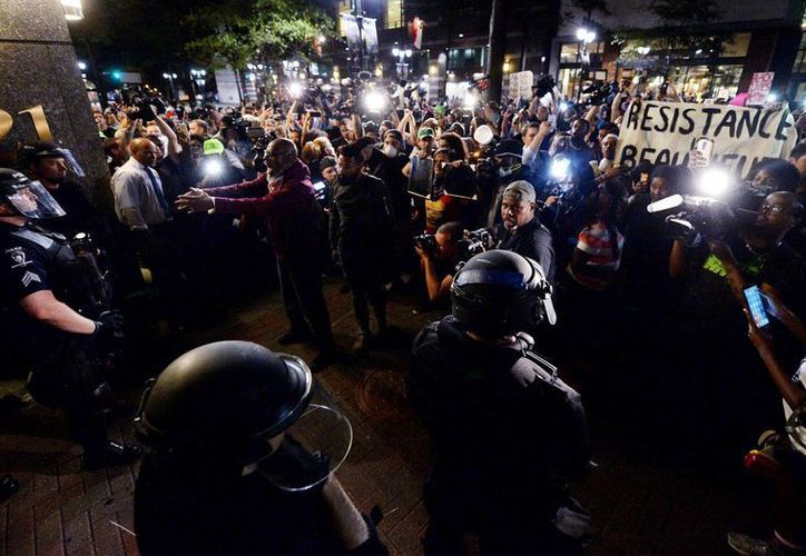Un grupo de manifestantes se enfrentaron a policias en  Charlotte, Carolina del Norte.  El toque de queda terminó el viernes, después de una noche de protestas por la muerte de Keith Lamont de Scott, que fue baleado por una oficial. (Jeff Siner / El observador de Charlotte a través de AP)