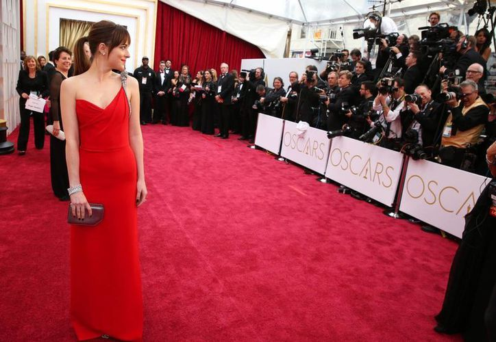 La actriz Dakota Johnson a su paso por la alfombra roja de la 87 entrega de los premios Oscar. (AP)