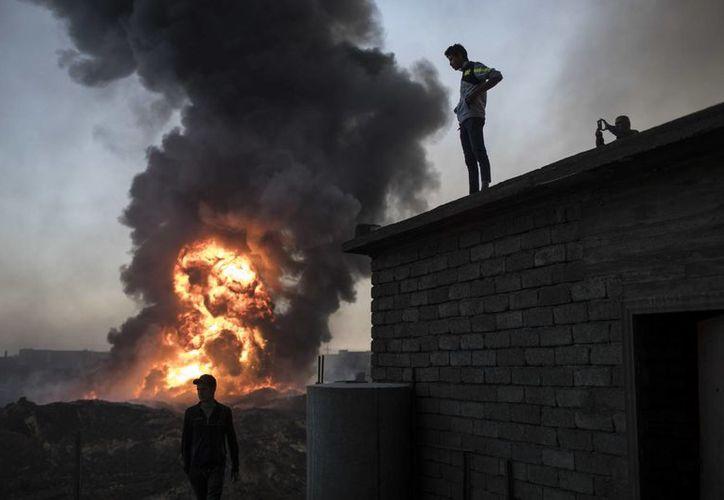 Gente mirando mientras personal de seguridad trata de extinguir un incendio de un campo petrolífero en Qayara, al sur de Mosul, Irak. (AP/Felipe Dana)