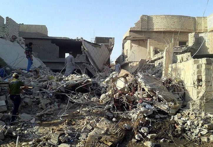 Un grupo de hombres inspecciona hoy las ruinas de un edificio tras un bombardeo de las Fuerzas Aéreas iraquíes en Faluya, Irak. (EFE)