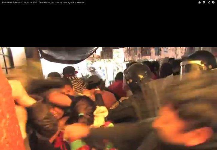 En primer plano se aprecia al granadero que se quitó el casco para golpear. (Captura de pantalla de YouTube)