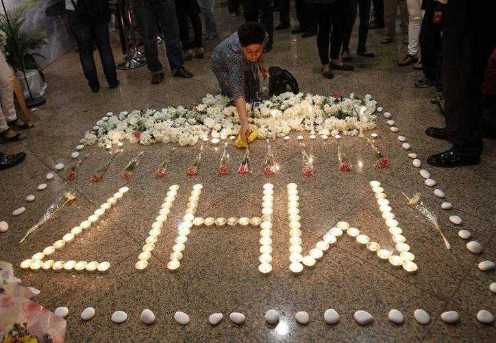 Un miembro de la tripulación de Malaysia Airlines deposita una vela junto a las demás que forman MH17 tras un servicio multireligioso por las víctimas del avión de la compañía derribado en Ucrania. (Agencias)