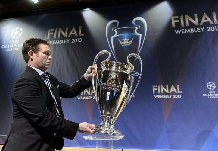 Un funcionario de la UEFA carga el trofeo de la Liga de Campeones tras el sorteo que involucra a los 16 equipos calificados. (Agencias)