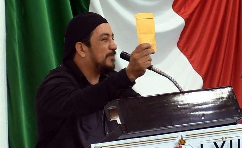 El diputado Charlie Valentino enseña el sobre donde incluyó su cooperación para pagar la deuda externa. (Foto: Agencia Reforma).