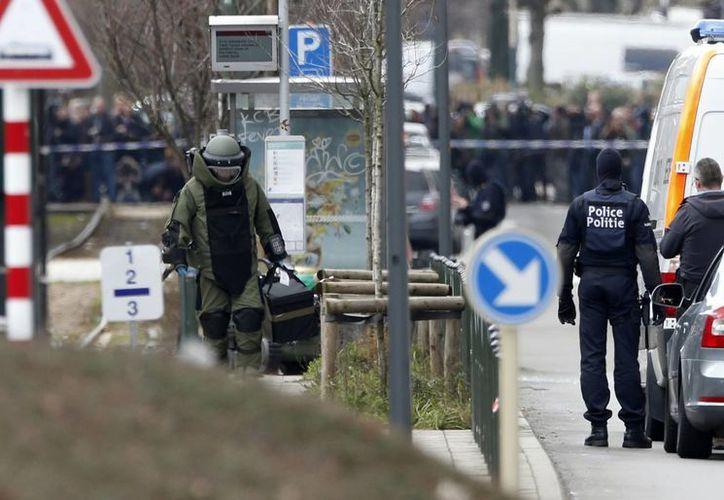 Un miembro de los servicios de emergencia (izq) protegido con un traje especial inspecciona un sitio en el distrito de Schaerbeek, en Bruselas, Bélgica, el viernes 25 de marzo de 2016. (AP)