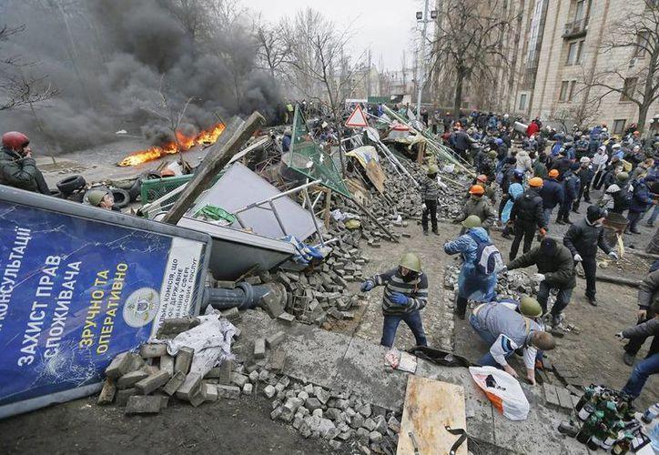 Numerosos manifestantes construyen una barricada después de los disturbios entre opositores y policía, en Kiev, Ucrania. (EFE)