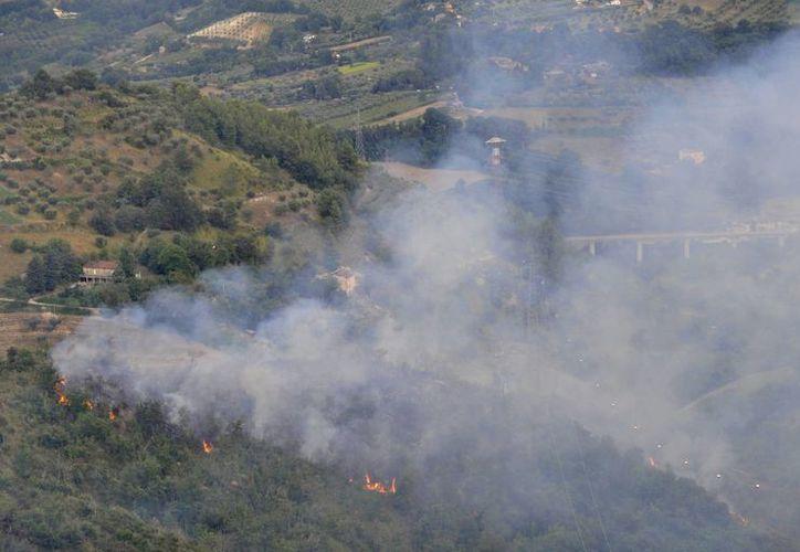 Imagen de las llamas en el sitio donde dos aviones militares de Italia se desplomaron tras chocar en el aire. (Agencias)
