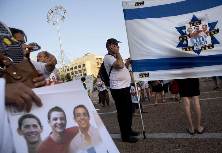 Israelíes sostienen la bandera nacional con las fotos de los tres jóvenes desaparecidos. (Agencias)
