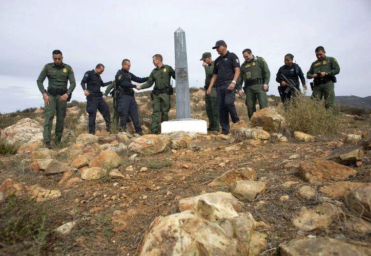 Unos agentes de la Patrulla Fronteriza y sus homólogos de la Policía Federal Mexicana se saludan durante un encuentro informal el 27 de octubre 2016, en las montañas de Otay, al este de San Diego, California y justo al norte del área conocida como Nido de las Águilas en Tijuana, México. (EFE)