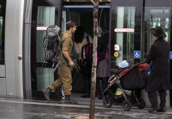 Un soldado israelí que lleva una kipá se sube a un vagón de un tren ligero en el barrio de French Hill, en Jerusalén, Israel. (EFE)