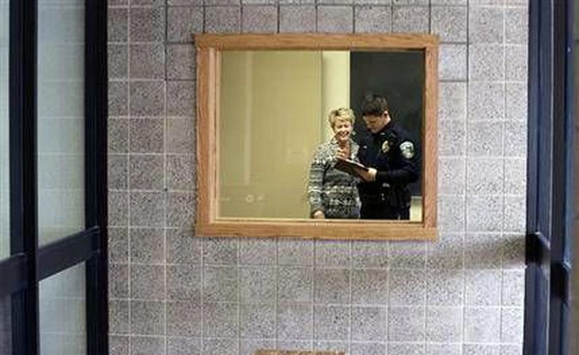 El policía Jeff Strack habla con la directora Stacy DeCorsey en una habitación que será preparada para que la ocupe la policía en la escuela primaria Jordan en Jordan. (Agencias)
