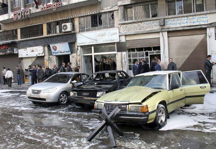 Varias personas observan los destrozos en una calle en Damasco. (EFE/Archivo)