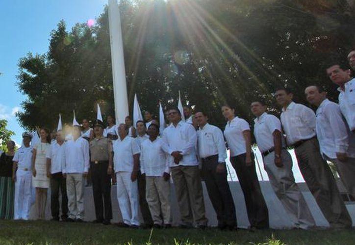 Momento en que integrantes de la Secretaría de la Marina colocan la majestuosa bandera. (Gustavo Villegas/SIPSE)