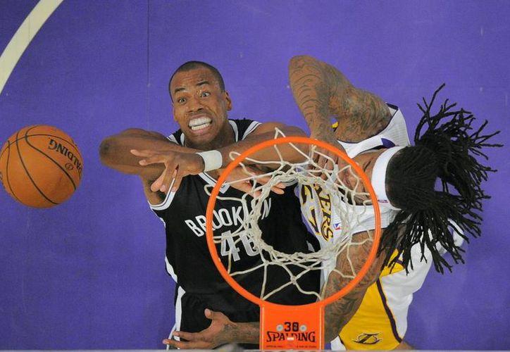 Jason Collins (i) trata de recuperar un rebote frente a Jason Hill, de Lakers de Los Angeles, en partido desarrollado en febrero de este año. (Foto: AP)