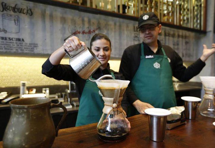 Empleados de Starbucks demuestran la preparación de café en el primer Starbucks que se inaugura en Bogotá, Colombia. (Agencias)