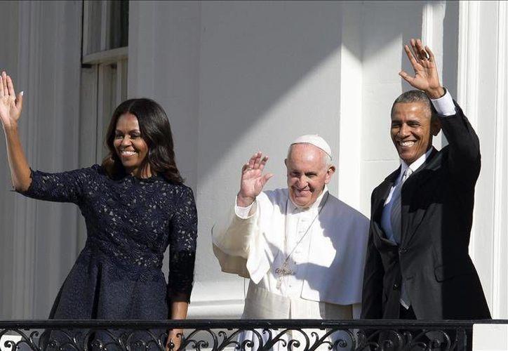 Michelle Obama, el Papa Francisco y Barack Obama saludan desde el balcón de la Casa Blanca a las cerca de 15 mil personas que asistieron al mensaje del Sumo Pontifice, en su visita a la capital de Estados Unidos. La gira papal continuará por las ciudades de Nueva York y Filadelfia. (EFE)