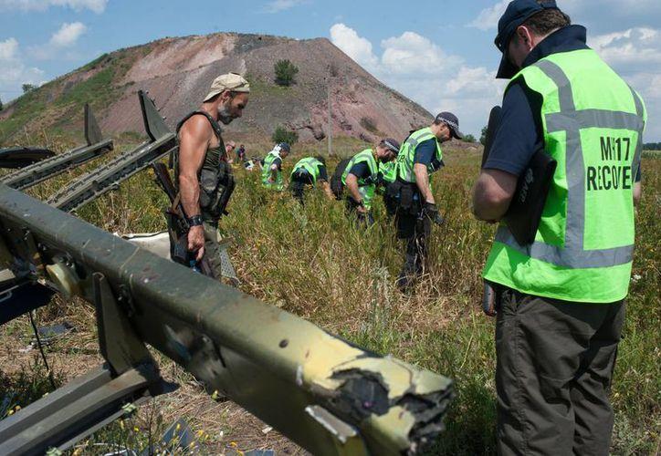 Un rebelde pro ruso vigila mientras investigadores de Malasia, Australia y Holanda examinan el área donde cayó el avión de Malaysia Airlines en el este de Ucrania. (Agencias)