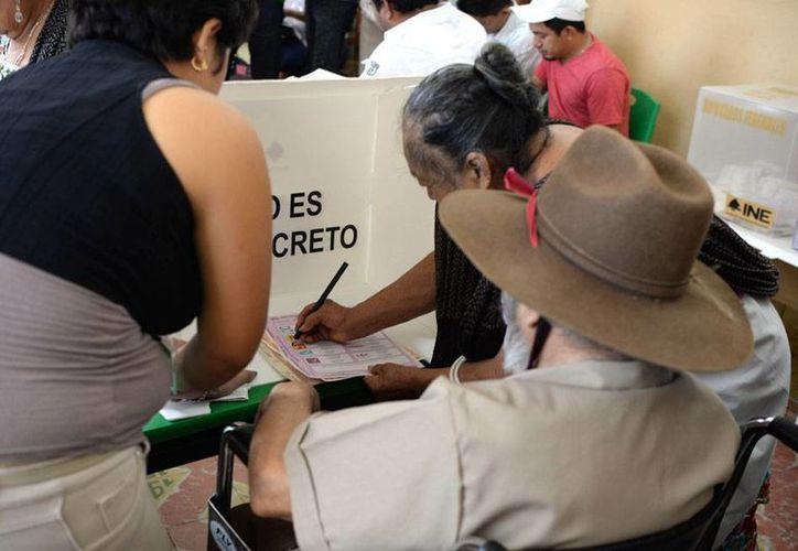 Varios gobernadores de México coincidieron en que es importante salir a votar, por lo que exhortaron a los ciudadanos ejercer su derecho. En la imagen, personas ayudan a un adulto mayor, discapacitado, a votar, en una casilla de Yucatán. (Cuauhtémoc Moreno/SIPSE)