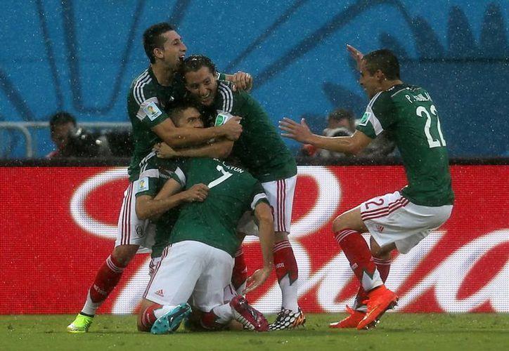 Oribe (semioculto, en cuclillas) dio tres puntos a México con su gol ante Camerún en el Mundial de Brasil. (Foto: AP)