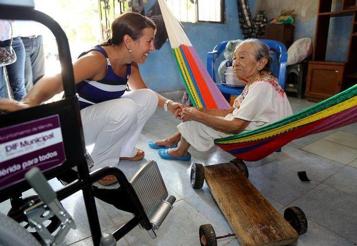 Una mujer de la tercera edad recibe una silla de ruedas de manos de la representante del DIF Municipal de Mérida,  Diana Castillo Laviada. (Milenio Novedades)