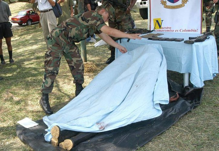 """Según las primeras informaciones, la operación se realizó para capturar a alias """"Javier"""", segundo cabecilla del frente 29 de las FARC. Imagen de archivo en el momento que un militar cubre con una sábana el cadáver de uno de sus compañeros del ejército colombiano. (EFE/Archivo)"""