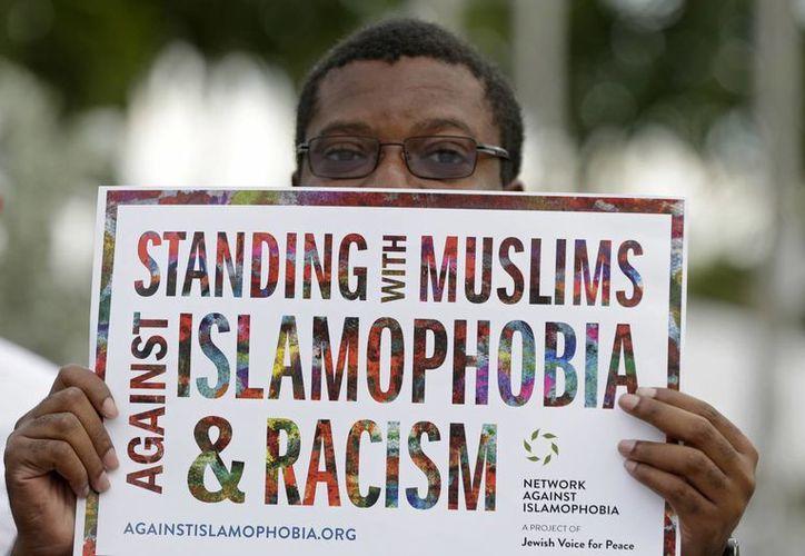 Un manifestante sostiene un cartel que dice 'de pie con los musulmanes en contra de la islamofobia y el racismo' durante una protesta contra un decreto del presidente Donald Trump a fin de frenar la inmigración de musulmanes. (AP/Alan Díaz)