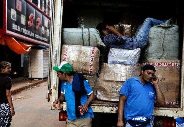 Trabajadores esperan para cargar mercancía en un camión en Ciudad del Este, Paraguay. (Agencias)
