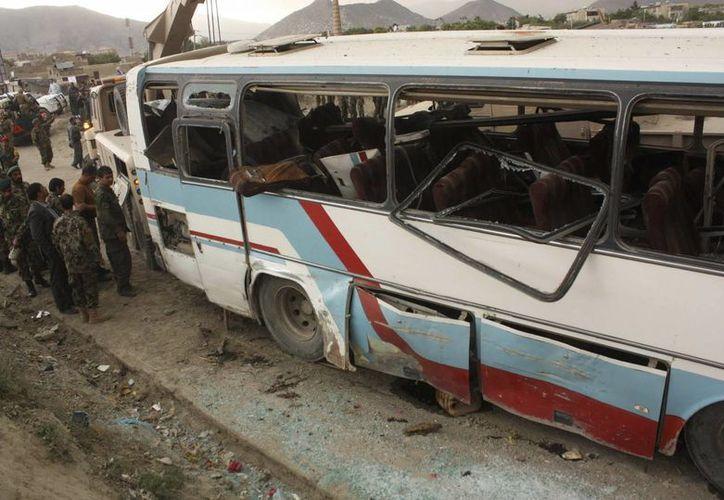Varios miembros de las fuerzas de seguridad afganas inspeccionan el lugar de un atentado en Kabul, este lunes. (EFE)